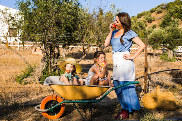 Mother and her two daughter sitting in wheelbarrow eating red apple