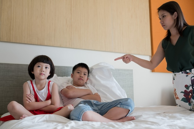 Mother hit her kid, two children crying, little girl and boy cry, feeling sad, young child unhappy, selective focus and soft focus