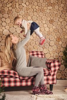 赤ん坊の娘を手に持って、冬のソファの素朴な居心地の良い部屋で彼女と遊んでいる母親