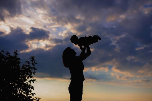 空の背景に赤ちゃんを抱いて母 Premium写真