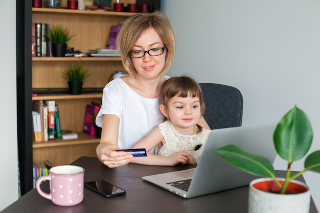 Мать держит кредитную карту с маленькой дочерью, сидя рядом, глядя на ноутбук. концепция покупок в интернете.
