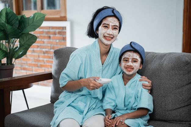 집에서 휴식을 취하는 동안 얼굴 마스크를 만들 때 얼굴 크림의 작은 접시와 기모노 타월을 입은 어린 소녀를 들고 어머니
