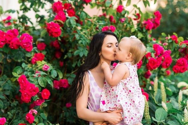 Мать держит и целует дочь на фоне красных роз