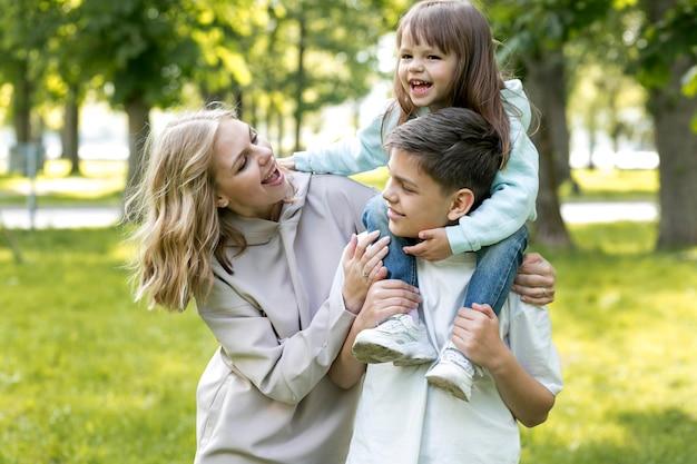 Мать держит и играет со своей дочерью и сыном