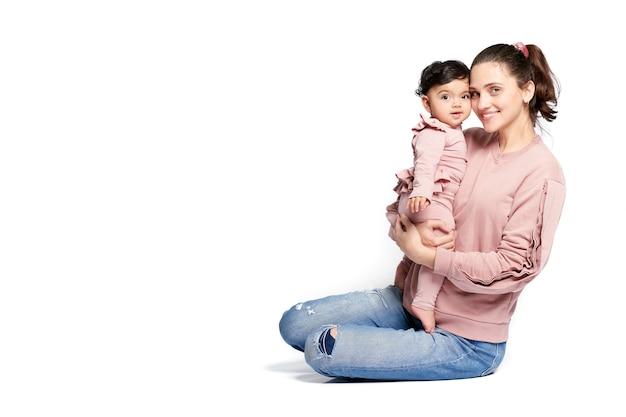 바닥에 앉아있는 동안 아기 딸을 들고 어머니