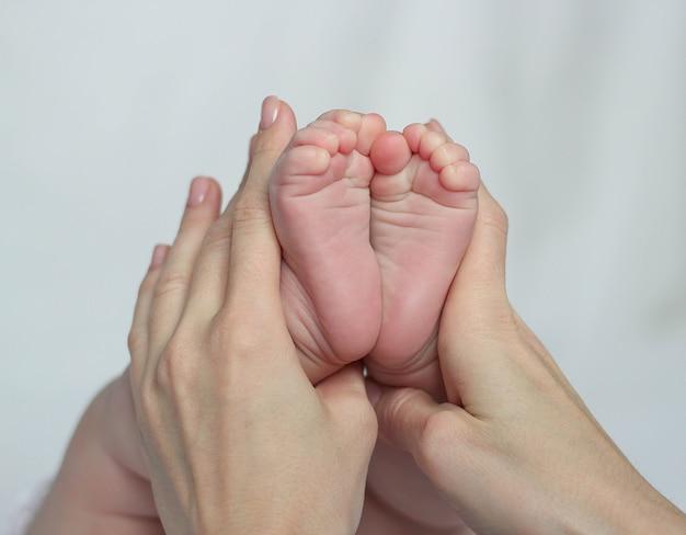 Мать держит ножки младенца, есть концепция или идея любви, семьи и счастья в доме, как мать, ухаживающая за новорожденным