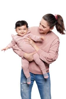 흰 벽에 고립 된 여자 아기를 들고 어머니