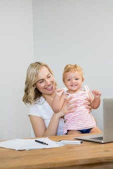 Mother holding baby girl while using laptop