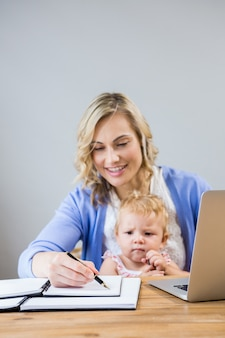 Mother holding baby girl while writing notes in personal organizer
