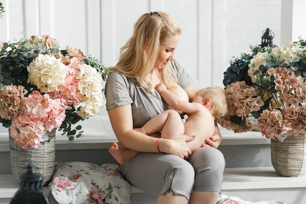 Мать, держащая ребенка на коленях перед грудным вскармливанием. студия в цветочном декоре