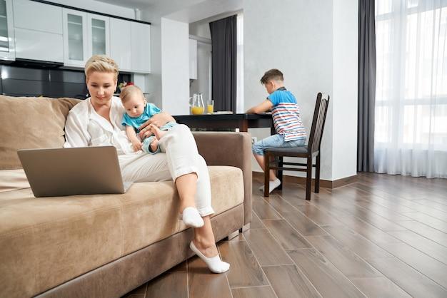 노트북과 함께 소파에 앉아있는 동안 어머니 지주 아기