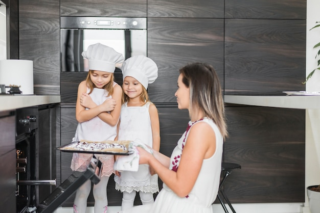 Mother holding baked cookies in tray while looking at her daughters
