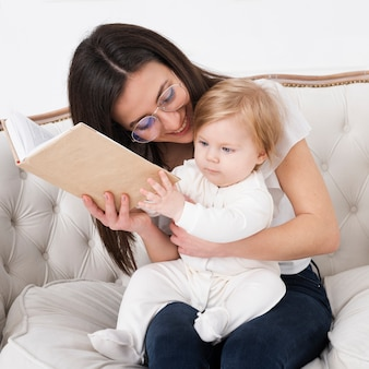 Mother holding book and baby