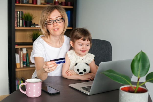 Mother holding a credit card with her little daughter sitting near looking at the laptop. shopping online concept.