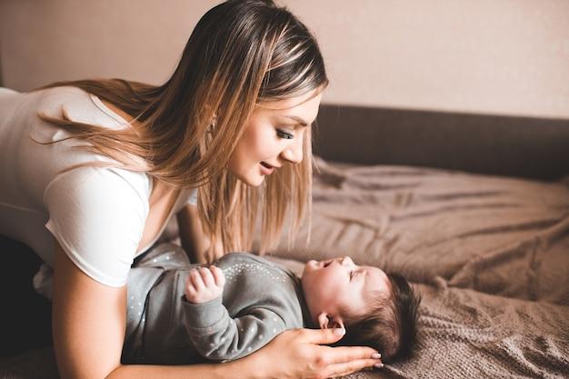 방에 침대에 누워 우는 아기를 들고 어머니. 불행한 아이. 서로 찾고. 어머니.