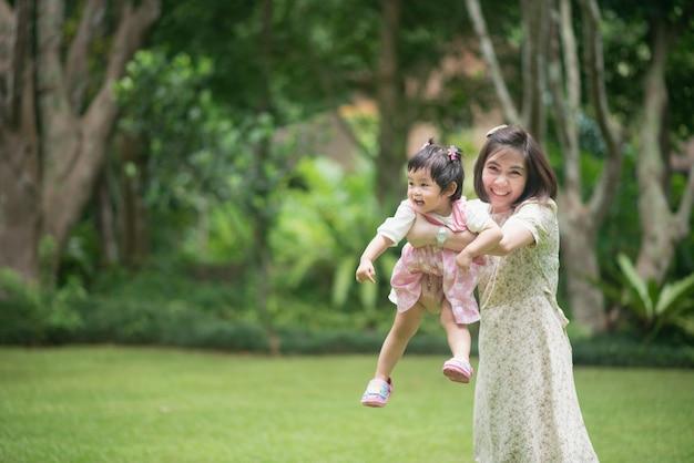 庭でかわいい赤ちゃんを持つお母さん