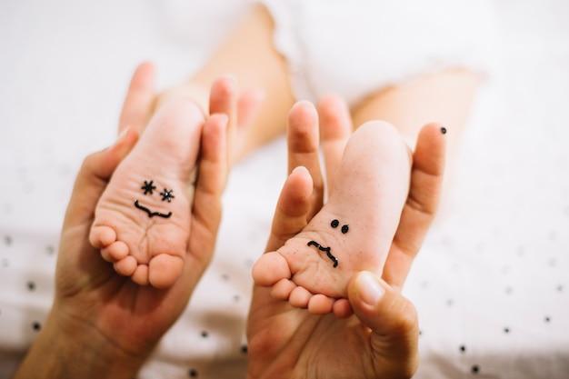 Мать, держащая ноги ребенка с смайликами