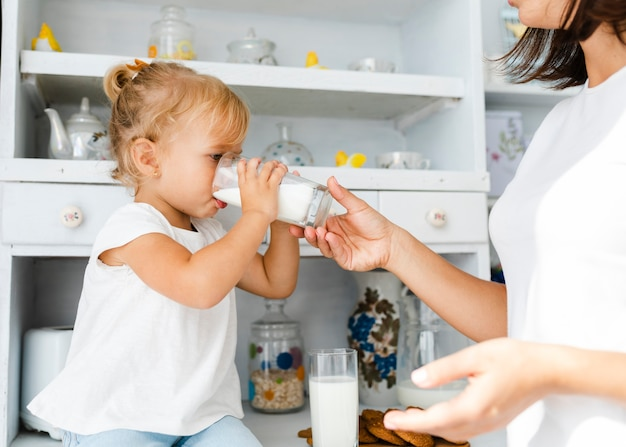 Mother holding a glass of milk fer her daughter