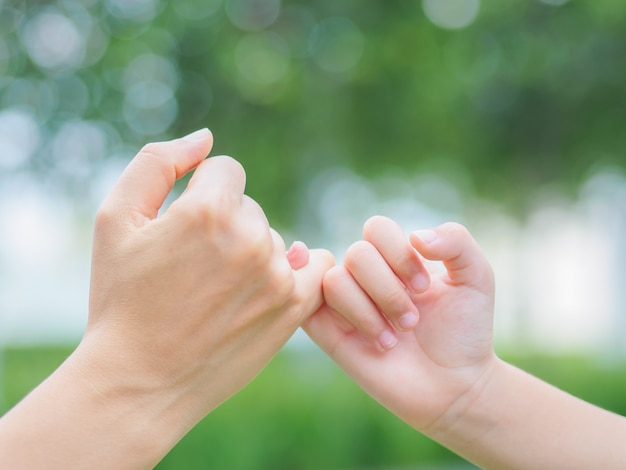 Mother holding a hand of her kid in spring day outdoors with green field background