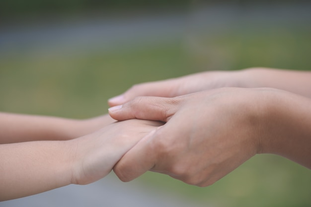 Mother holding a hand of his son with green glass background. love , family and mother day