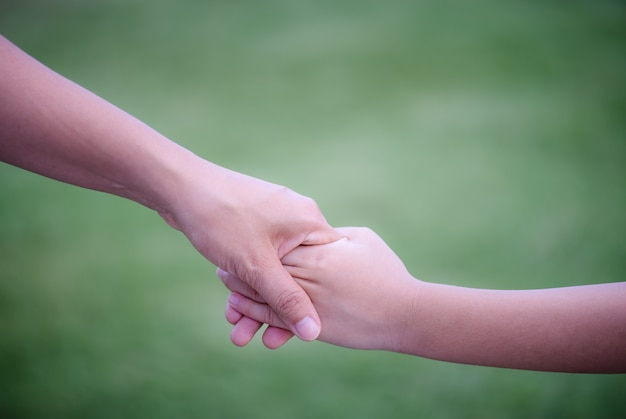 Mother holding a hand of his son with green glass background.