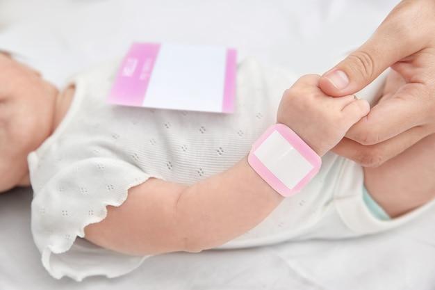 家で赤ちゃんの手をつなぐお母さん