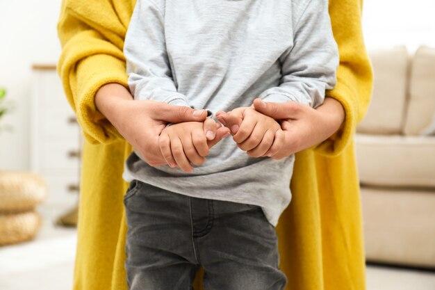 실내, 근접 촬영 그녀의 아이와 손을 잡고 어머니. 행복한 가족