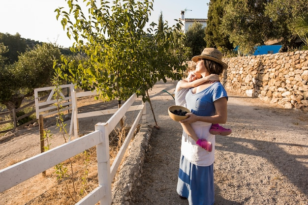 Mother holding harvested olives in the bowl with her daughter