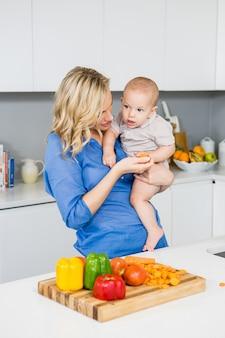 母は台所で彼女の男の子を保持します