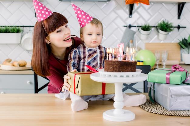 誕生日ケーキと彼女の赤ん坊の娘を持つお母さん