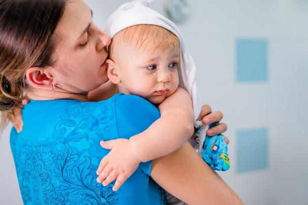 入浴後、赤ちゃんを抱っこしている母親。