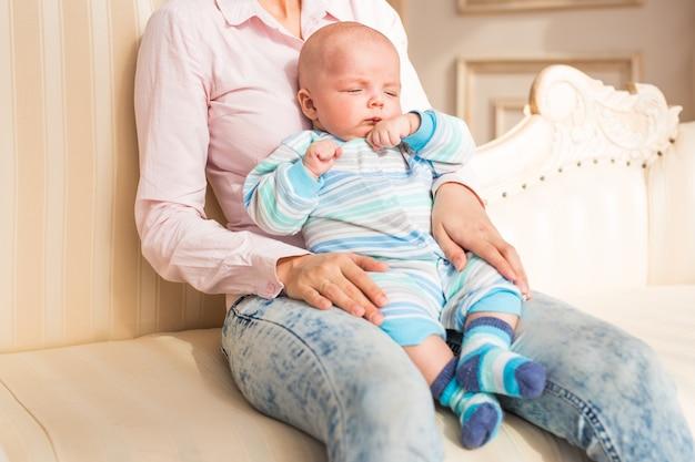 部屋で彼女の赤ん坊の息子を保持している母親