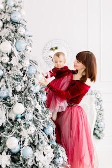 그녀의 귀여운 작은 딸을 들고 크리스마스 트리를 장식하는 어머니