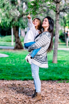 母は彼女の娘を保持し、美しい朝に公園で遊んで