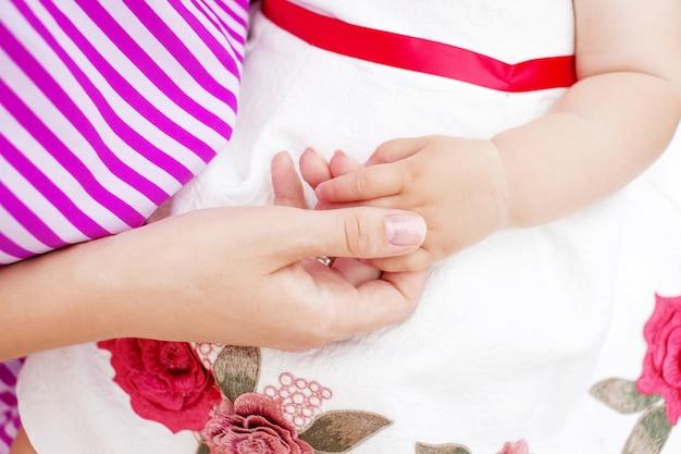 母は彼女の娘の手を握っています。幸せな家族