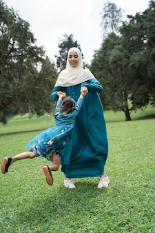 Mother holding her daughter and spin around happily