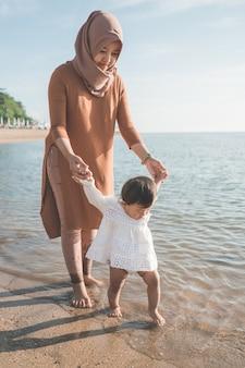 해변에 산책 그녀의 딸을 들고 어머니