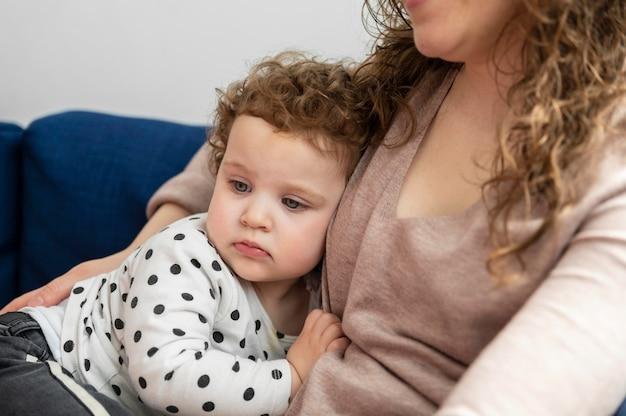 Мать держит своего маленького ребенка на диване