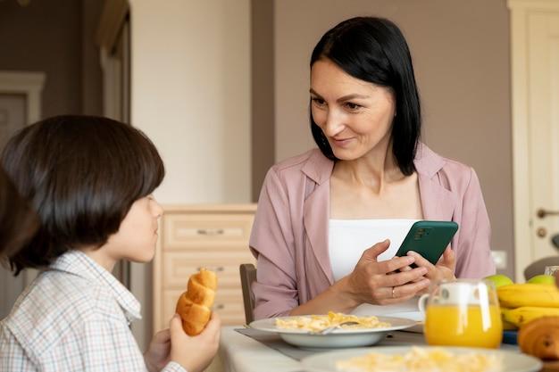 그녀의 아들 옆에 그녀의 스마트폰을 들고 어머니
