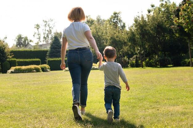 Мать держит сына за руку сзади