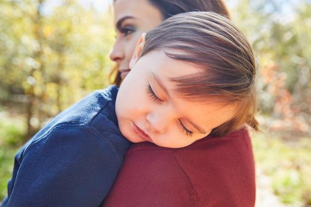 Mother holding kid boy sleeping in her shoulder