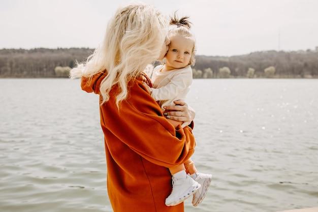 Мать держит маленькую дочь на руках, целуя ее в щеку