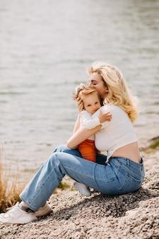 暖かい春の日に湖のそばに座って屋外で小さな娘を腕に抱く母親