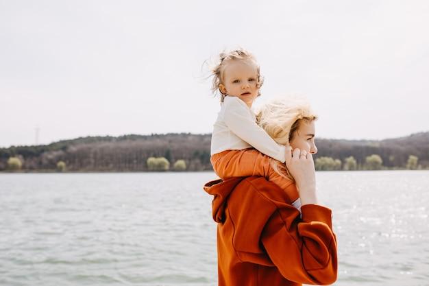 Мать держит маленькую дочь на плечах, проводя время с семьей на озере
