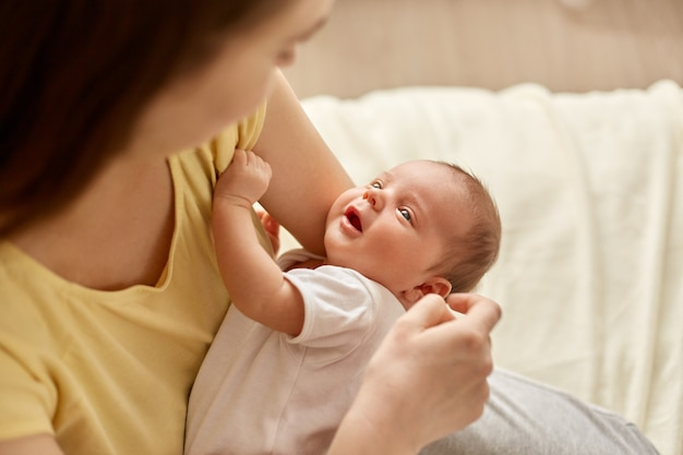 Мать держит новорожденного девочку или мальчика, женщина в желтой футболке смотрит на своего младенца с любовью, обнимает своего ребенка, дочь или сына смотрит на маму.