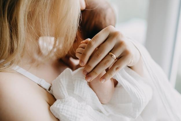生まれたばかりの赤ちゃんの手を握って母