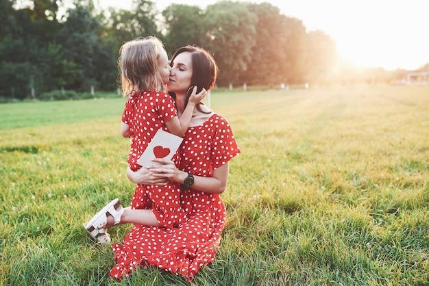 어머니는 그녀의 손에 종이 책과 소녀를 들고 그녀에게 키스를 제공