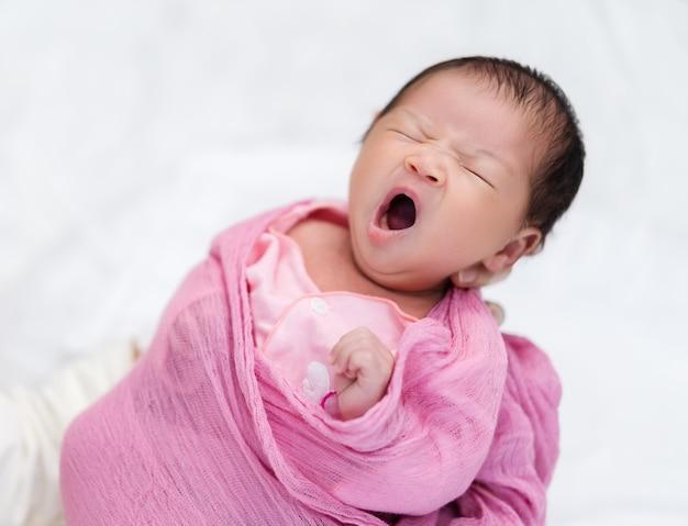 Мать держит сонного новорожденного, зевая в руке
