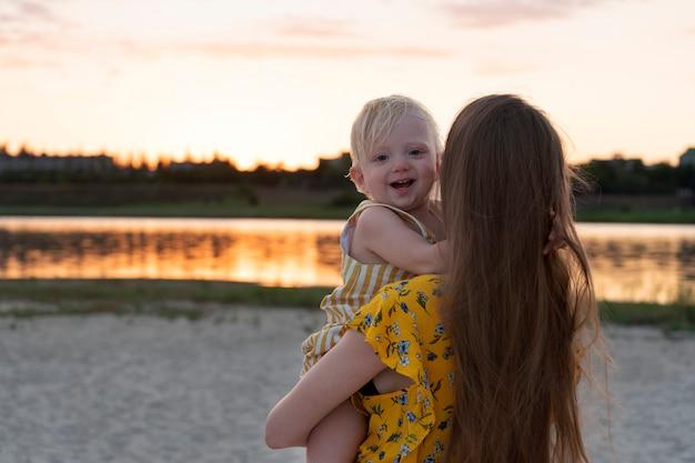 Мать держит улыбающегося ребенка перед рекой на закате.