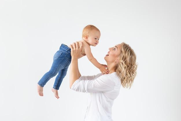 白い壁に甘い女の赤ちゃんを保持している母